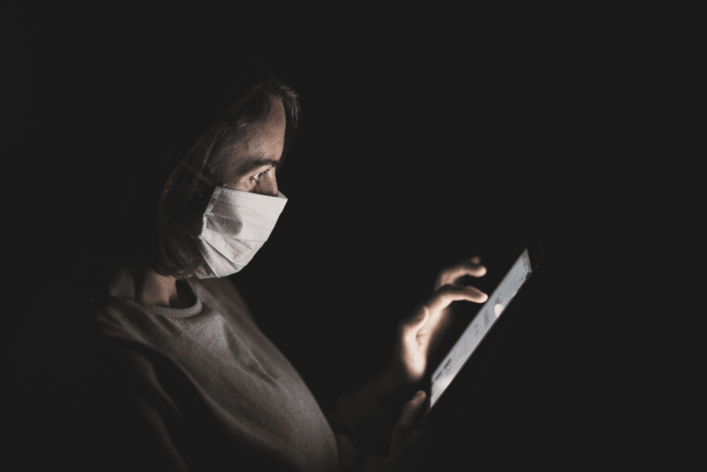 Woman wearing surgical mask during pandemic using her cell phone to access insurance services