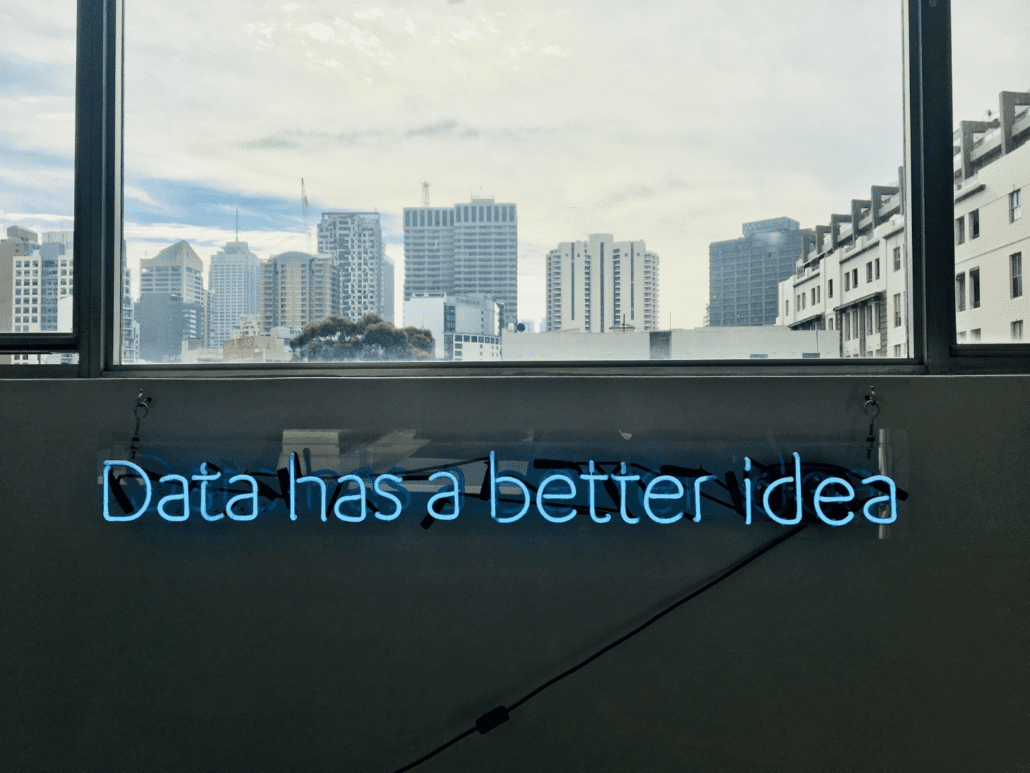 "Neon sign saying ""data has a better idea"" with city in the background"