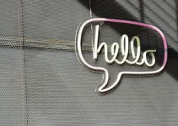 """Neon sign of a chat bubble with the word """"Hello!"""""""